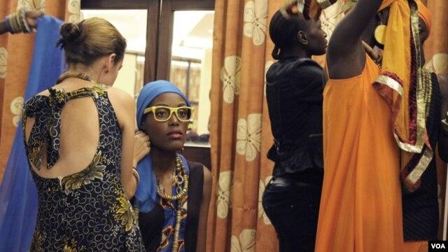 Models wearing East African designer clothing prepare for a runway show in Kampala, Uganda, May 17, 2014. (Hilary Heuler / VOA News)