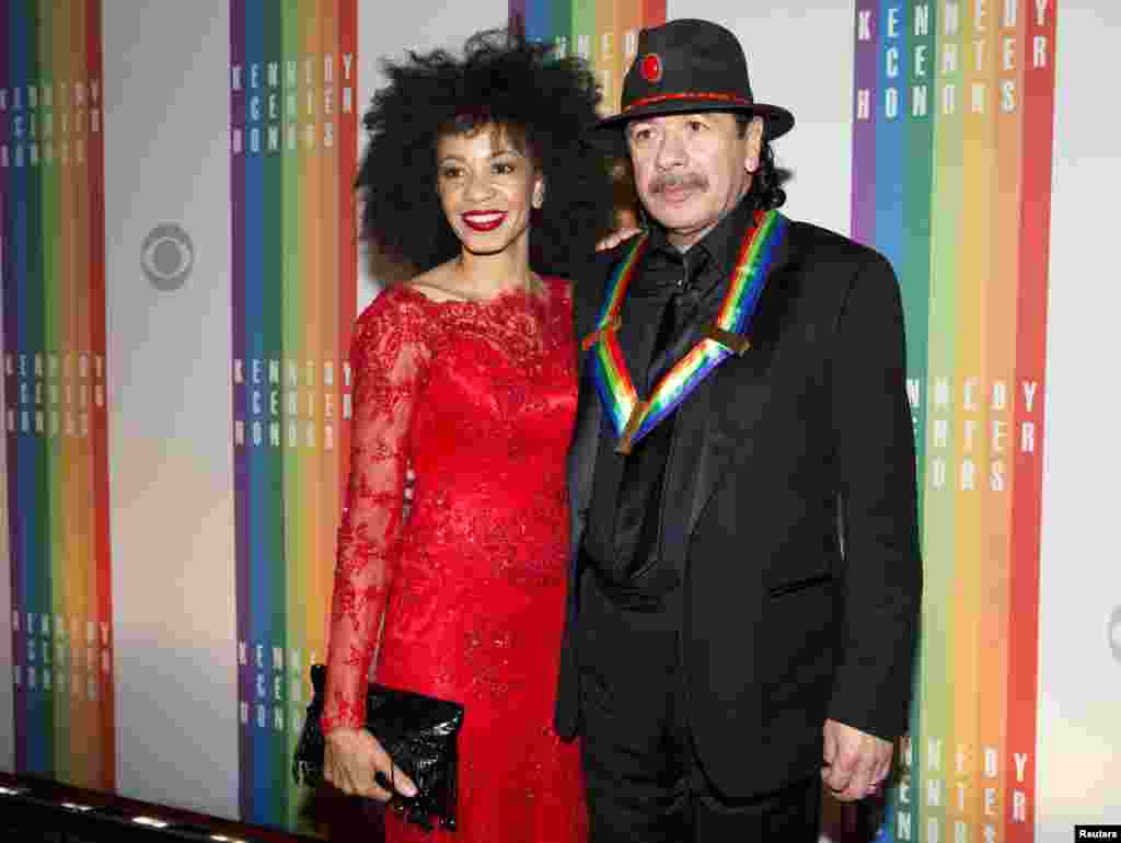 Kennedy Center Honoree Carlos Santana and his wife Cindy Blackman arrive for the Kennedy Center Honors in Washington, Dec. 8, 2013.