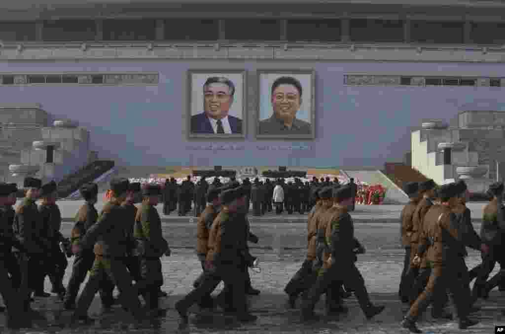 Para tentara Korea Utara berbaris di alun-alun Kim Il Sung di Pyongyang sementara warga memberi penghormatan di bawah potret-potret mendiang pemimpin mereka Kim Jong Il dan Kim Il Sung (17/12). (AP/David Guttenfelder)