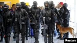 FILE - Members of Brazil's Battalion of Special Operations (BOPE) participate during a crisis simulation exercise conducted by the BOPE to show the media how security will be provided during the 2016 Olympics at the Golf Olympic bus station in Rio de Janeiro, Feb. 11, 2015.