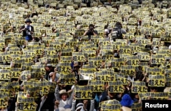 Japanese protesters raise placards reading 'Anger was over the limit' during a rally against U.S. military bases, following the arrest of an American suspected of murdering a local woman, June 19, 2016.