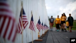Visitors to the Flight 93 National Memorial pauses at the Wall of Names containing the names of the 40 passengers and crew of United Flight 93 that were killed in this field on Sept. 11, 2001, on Thursday, May 31, 2018. Later this year, the remaining wreckage of Flight 93 will be returned to the Flight 93 National Memorial to be buried in the restricted access zone, in the woods beyond the Wall of Names marked by a giant boulder, where they will not be accessible to the public or media.