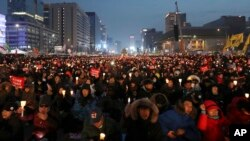 """Protesters hold candles during a rally calling for South Korean President Park Geun-hye to step down in Seoul, South Korea, Dec. 24, 2016. The letters read """"Arrest, Park Geun-hye."""""""