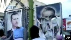 ພວກປະທ້ວງທີ່ເມືອງ Qamishli ໃນພາກຕາເວັນອອກສຽງເໜືອຂອງຊີເຣຍ ພາກັນຈີກຮູບໂປສເຕີ້ຂອງປະທາ ນາທິບໍດີ Bashar al-Assad (ຊ້າຍ) ແລະມື້ລາງທ່ານ Hafez Assad ບິດາຂອງທ່ານ (30 ເມສາ 2011)