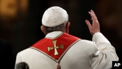 Pope Francis waves as he presides over the Via Crucis (Way of the Cross) torchlight procession on Good Friday in front of Rome's Colosseum, April 14, 2017.