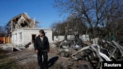 Seorang laki-laki berdiri di depan puing-puing sebuah rumah yang rusak akibat serangan senjata berat di Donetsk, Ukraina timur (6/11/2014).