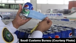Saudi Customs' officer cuts open Pepsi labels from cans and finds they are actually beer.