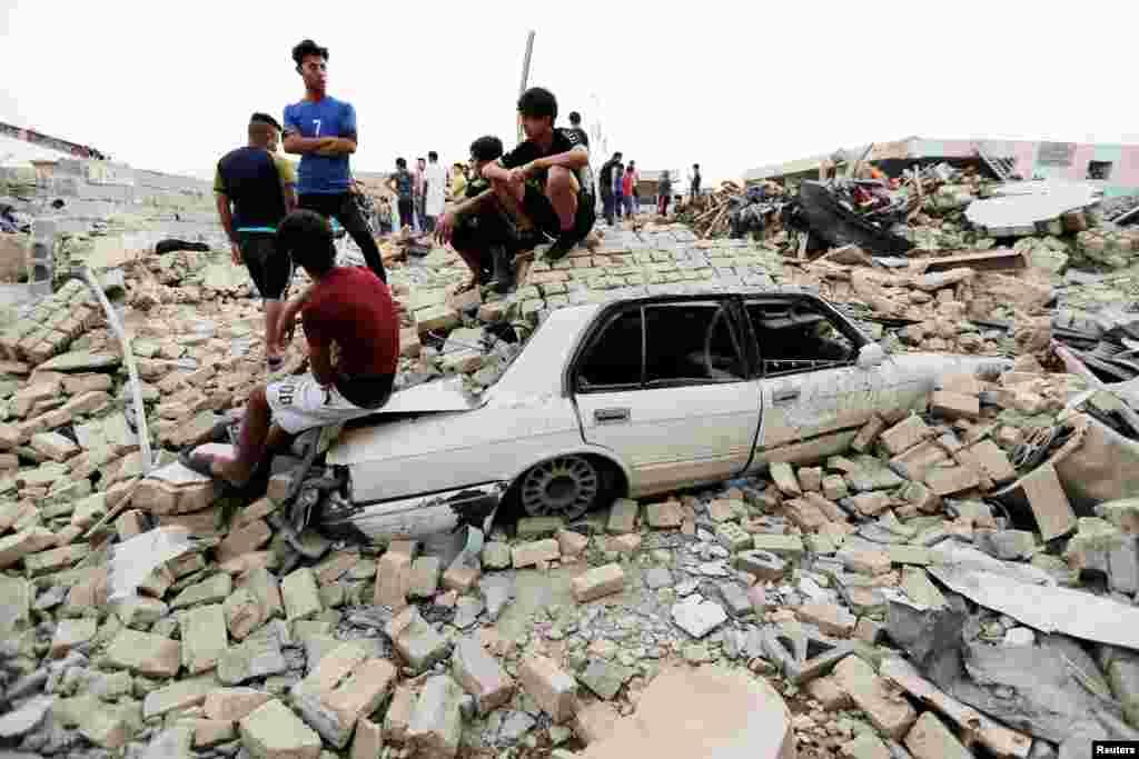 Bağdat'taki bir patlama sonrası gençler, yıkıntılar üzerinde duruyor.