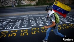 Un manifestante porta su bandera sobre una calle con los nombres de las víctimas de la violencia en Venezuela.