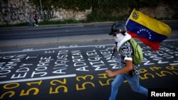 Un manifestante llevando una bandera venezolana corre junto a una lista de las víctimas de la violencia durante protestas contra el gobierno del presidente de Venezuela, Nicolás Maduro en Caracas. Junio 12 de 2017.