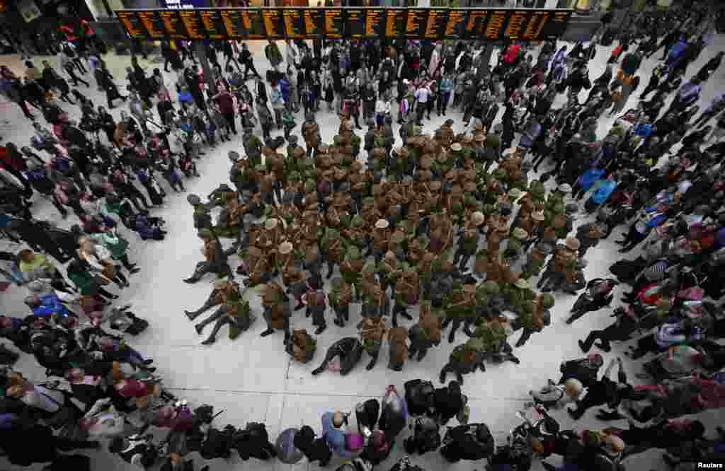 Actors dressed in World War 1 army fatigues gather in a group at Waterloo Station, to commemorate the start of the Battle of The Somme, in London, Britain.