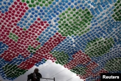 FILE - A worker stands next to an installation made of plastic bottles in Tegucigalpa March 31, 2015. The Museum of National Identity is working on installations made from recycled plastic bottles as a way to encourage recycling in the community, local media rep