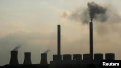 FILE - Smoke rises from the Duvha coal-based power station owned by state power utility Eskom, in Mpumalanga province, South Africa, Feb. 18, 2020.