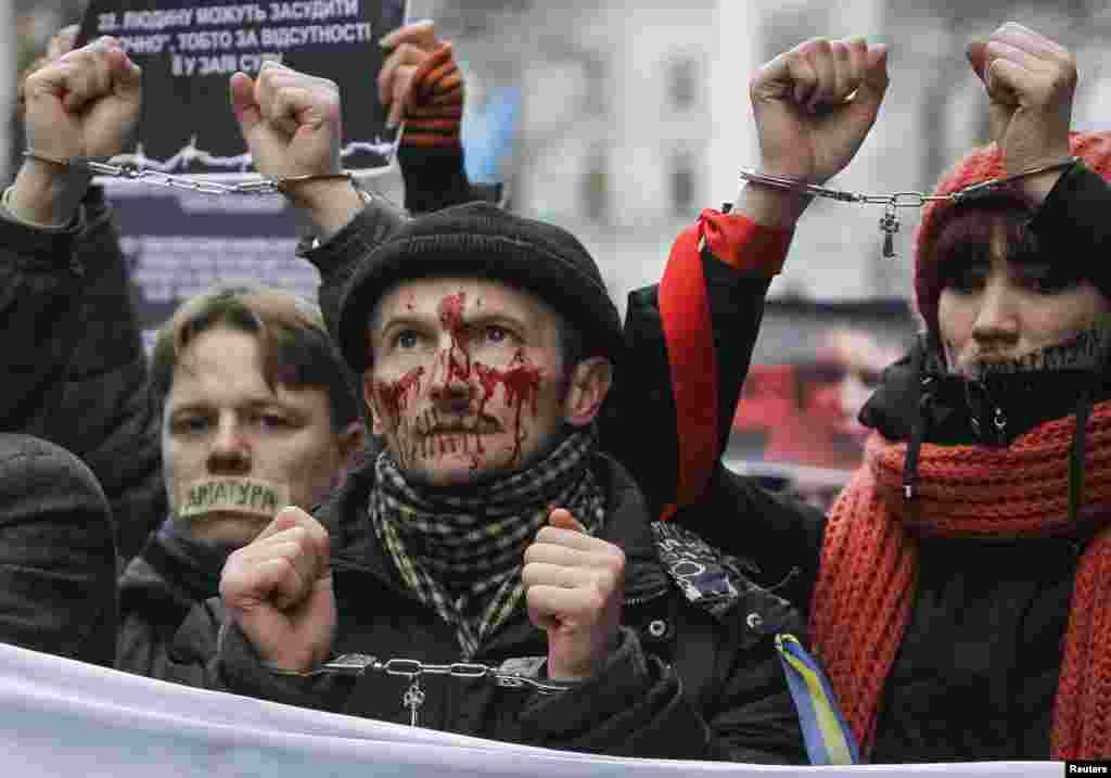 Những người ủng hộ hội nhập thân châu Âu với băng keo dán miệng tham dự một cuộc biểu tình chống lại những đạo luật mới được thông qua tại Kiev, Ukraina. Những người ủng hộ Tổng thống Ukraina Yanukovich thông qua một đạo luật bao quát tại Quốc hội nhằm ngăn chặn những cuộc biểu tình chống chính phủ.