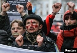 Pro-European integration supporters with taped mouths attend a rally against newly approved laws near the presidential administration in Kyiv, Ukraine, Jan. 17, 2014.