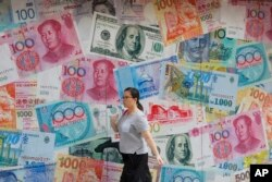 A woman walks by a money exchange shop decorated with different countries currency banknotes at Central, a business district in Hong Kong, Tuesday, Aug. 6, 2019.