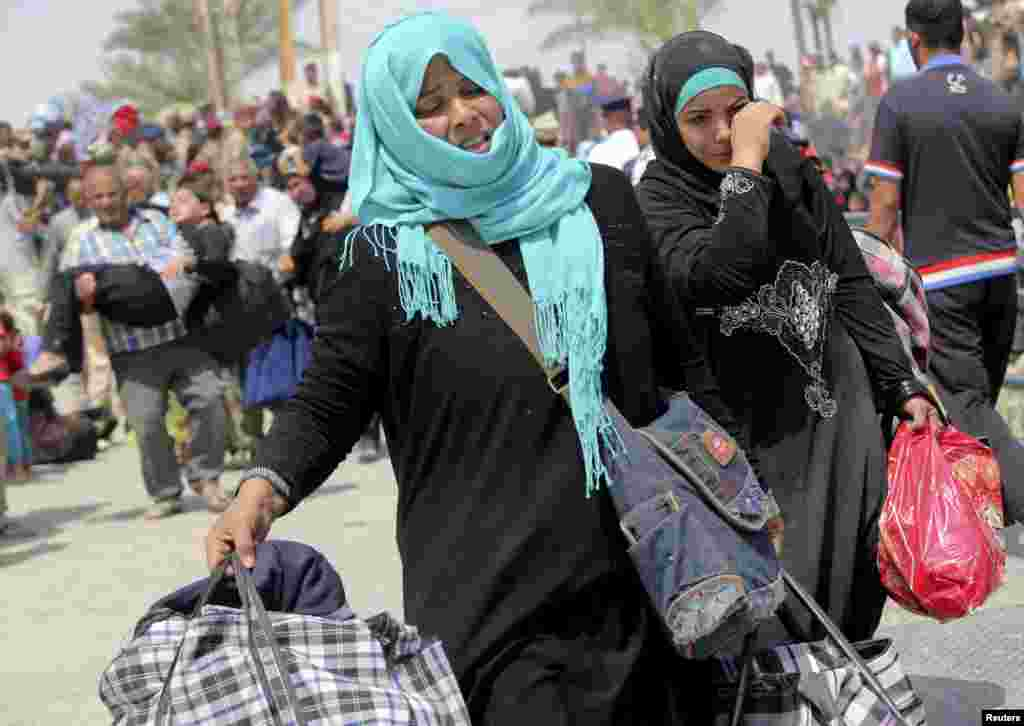 Displaced Sunni women fleeing the violence in Ramadi carry bags as they walk on the outskirts of Baghdad, May 24, 2015.