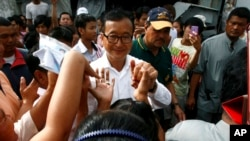 Sam Rainsy, center, leader of Cambodia National Rescue Party greets villagers while visiting a polling station at Chak Angre Leu pagoda, in Phnom Penh, Cambodia, Sunday, July 28, 2013.