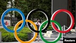 Seorang perempuan yang mengenakan masker pelindung di tengah wabah Covid-19 mengambil gambar logo Olimpiade di depan Stadion Nasional di Tokyo, Jepang, 14 Oktober 2020. (Foto: Reuters)