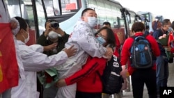 A medical worker from China's Jilin Province, in red, embraces a colleague from Wuhan as she prepares to return home at Wuhan Tianhe International Airport in Wuhan in central China's Hubei Province, Wednesday, April 8, 2020. (AP Photo/Ng Han Guan)