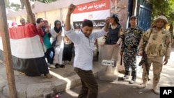 A man dances as women sing national songs in front of a polling station during the second day of the presidential in Cairo, Egypt, Tuesday, March 27, 2018.