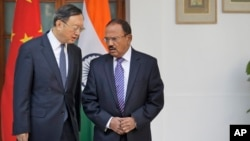 FILE - Indian National Security Adviser Ajit Doval, right, talks with Chinese State Councillor Yang Jiechi before their delegation-level meeting in New Delhi, India, Dec. 22, 2017.
