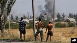 Residente locales observan el cañoneo en el pueblo de Novoazovsk, en el este de Ucrania.