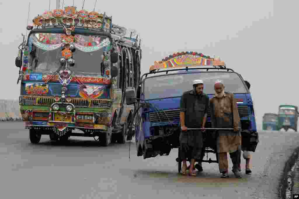 Pakistani laborers transport the front portion of a vehicle using a handcart at a road in Peshawar.