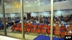 Буддистські монахи та інші особи слухають перебіг судової справи проти лідерів «червоних кхмерів»