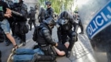 FILE - A protester is detained by riot police during an anti-government demonstration in Ljubljana, Slovenia, June 25, 2021.