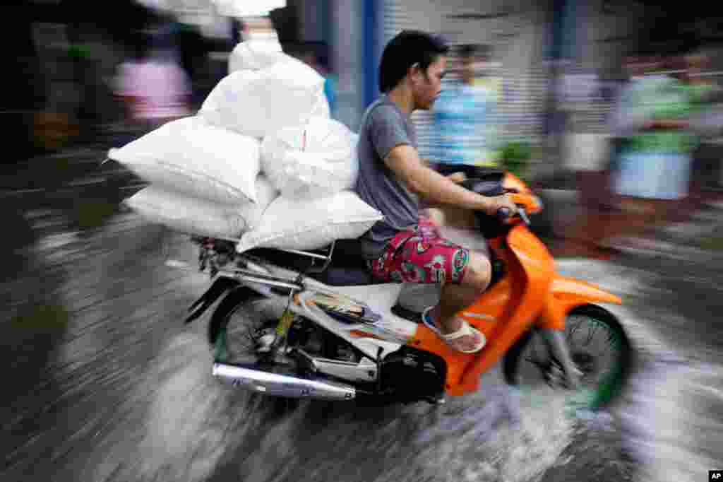 October 28: A man rides his motorcycle through flooded streets to deliver goods in Bangkok, Thailand. (AP Photo/Aaron Favila)