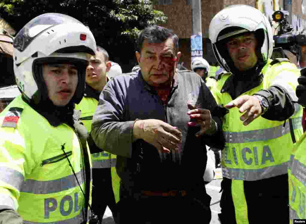 Un herido es auxiliado por policías colombianos, luego de un atentado en el distrito comercial de la capital.