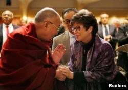 The Dalai Lama shakes hands with Valerie Jarrett, senior advisor to U.S. President Barack Obama, at the National Prayer Breakfast in Washington, Feb. 5, 2014.