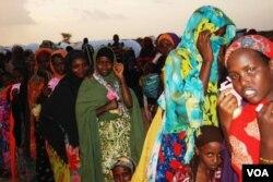 Ibu-ibu dan anak-anak mengantri makan malam di pusat transit pengungsi di Dollo Ado, Ethiopia (26/10).