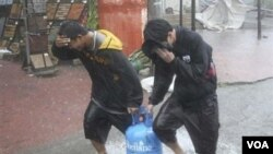 Dua warga Filipina melewati hujan besar kemarin yang akibatkan topan Megi di Cauayan, provinsi Isabela, Filipina bagian utara.