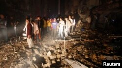 Residents and rescue workers gather at the site of a bomb blast in a residential area in Karachi March 3, 2013. A bomb attack in a Shi'ite Muslim area of Pakistan's commercial capital Karachi killed 25 people and wounded 50 on Sunday, the police said. REU