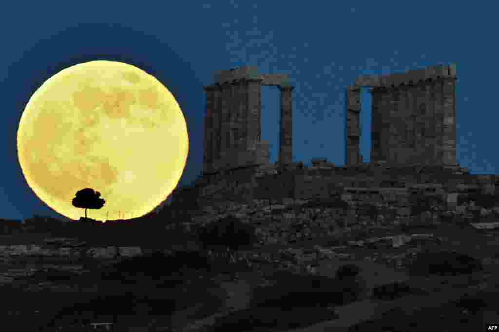 A supermoon rises behind the ancient Greek temple of Poseidon at Cape Sounion, some 65 kilometers south of Athens, Greece, June 23, 2013.