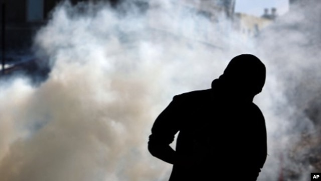 Anti-government protester runs from tear gas fired by riot police in A'ali, Bahrain, November 23, 2011.