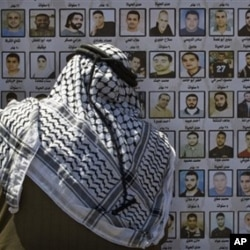 A Palestinian man looks at pictures of Palestinians imprisoned in Israeli jails, Thursday, April 15, 2010. Palestinians marked the annual prisoner's day by calling for the release of over 11,000 Palestinian prisoners, including women and children, curre