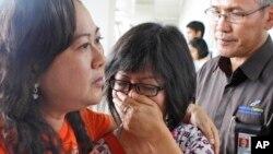 Yon paran youn nan pasaje ki te abò avyon AirAsia, vòl no. QZ8501, ap kriye nan ayewopò entènasyonal Juanda, nan vil Surabaya, Zile Java, Endonesi, pandan lap tann dènye nouvèl sou avyon ki disparèt la. (Foto: Dimanch 28 desanm 2014).