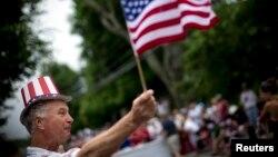Un hombrte levanta la bandera de EE.UU. durante el desfile en Massachusetts.