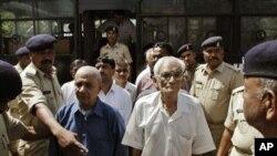 Polisi India mengawal para tersangka pelaku kerusuhan Godhra, Gujarat tahun 2002 di pengadilan distrik Anand, Gujarat (9/4).