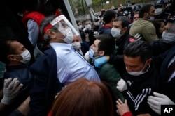 Seorang demonstran, mengenakan masker untuk melindungi diri terhadap virus corona, memberi isyarat saat didorong ke mobil polisi setelah ditangkap ketika berunjuk rasa dalam peringatan Hari Buruh di Istanbul, Jumat, 1 Mei 2020.