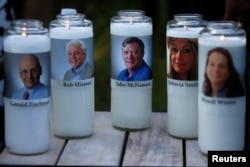 Candles representing the slain journalists of Capital Gazette sit on display during a candlelight vigil held near the Capital Gazette, the day after a gunman killed five people inside the newspaper's building in Annapolis, Maryland