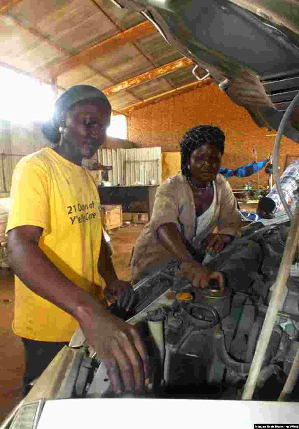 Car mechanics Elizabeth Yacob (L) and Diane Andrew service a vehicle at the University of Juba Auto Garage in the South Sudan capital.