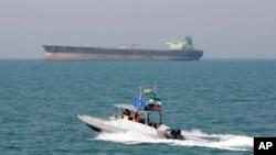 Perahu motor garda revolusi Iran melakukan patroli di Teluk Persia, sementara sebuah kapal tanker tampak di belakang (foto: ilustrasi).