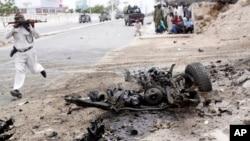 Seorang tentara Somalia lari untuk menembak dekat bangkai mobil yang meledak karena bom selama serangan ke parlemen Somalia (24/5). (AP/Farah Abdi Warsameh)