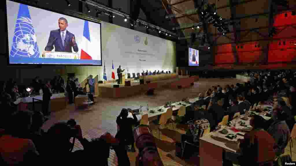 Le président américain Barack Obama visible sur un écran géant lors d'un discours qu'il prononce à la COP21 au Bourget, près de Paris, France, 30 novembre, 2015.