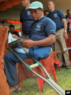 A former Khmer Rouge, injured, soldier reads a handout book on the history of the Khmer Rouge regime.