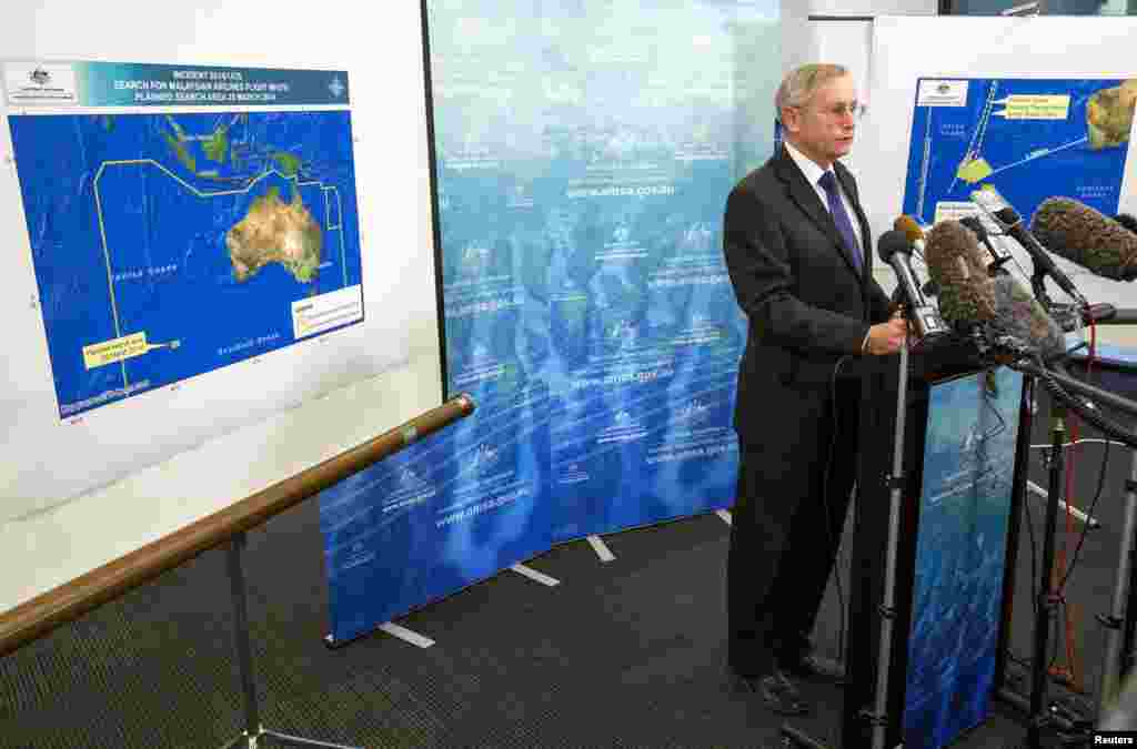 John Young, general manager of the emergency response division of the Australian Maritime Safety Authority, answers a question as he stands in front of a diagram showing the search area for flight MH370 during a briefing in Canberra, March 20, 2014.